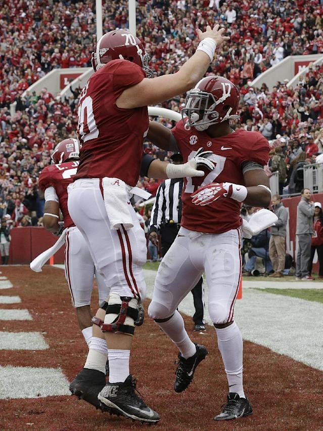 Alabama running back Kenyan Drake (17) celebrates with offensive linesman Ryan Kelly (70) after scoring on a 13-yard touchdown run against Chattanooga during the first half of an NCAA college football game in Tuscaloosa, Ala., Saturday, Nov. 23, 2013. (AP Photo/Dave Martin)