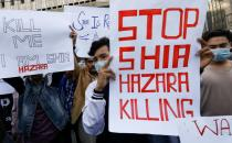 People carry placards demanding justice during a protest in Karachi