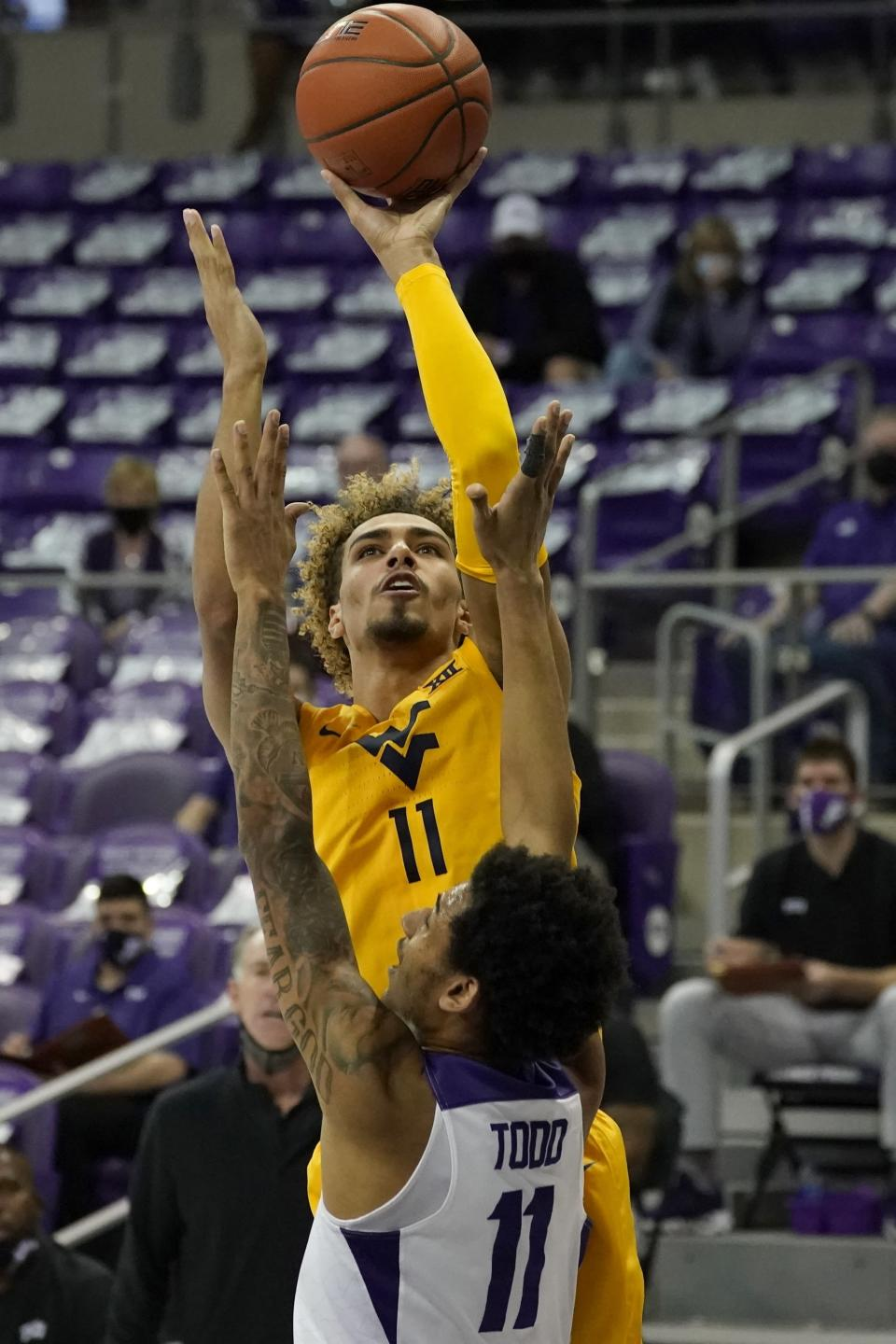 West Virginia forward Emmitt Matthews Jr., top, takes a shot as TCU guard Taryn Todd, bottom, defends in the first half of an NCAA college basketball game in Fort Worth, Texas, Tuesday, Feb. 23, 2021. (AP Photo/Tony Gutierrez)