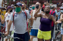 A woman shouts during a an anti-government protest in Havana, Cuba, Sunday, July 11, 2021. Hundreds of demonstrators went out to the streets in several cities in Cuba to protest against ongoing food shortages and high prices of foodstuffs. (AP Photo/Ismael Francisco)