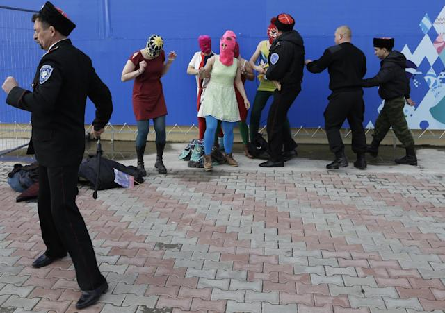 Members of the punk group Pussy Riot, including Maria Alekhina in the pink balaclava, center, are attacked by Cossack militia in Sochi, Russia, on Wednesday, Feb. 19, 2014. The group had gathered to perform in a downtown Sochi restaurant, about 30km (21miles) from where the Winter Olympics are being held. They left the restaurant wearing bright dresses and ski masks and had only been performing for a few seconds when they were set upon by Cossacks. (AP Photo/Morry Gash)
