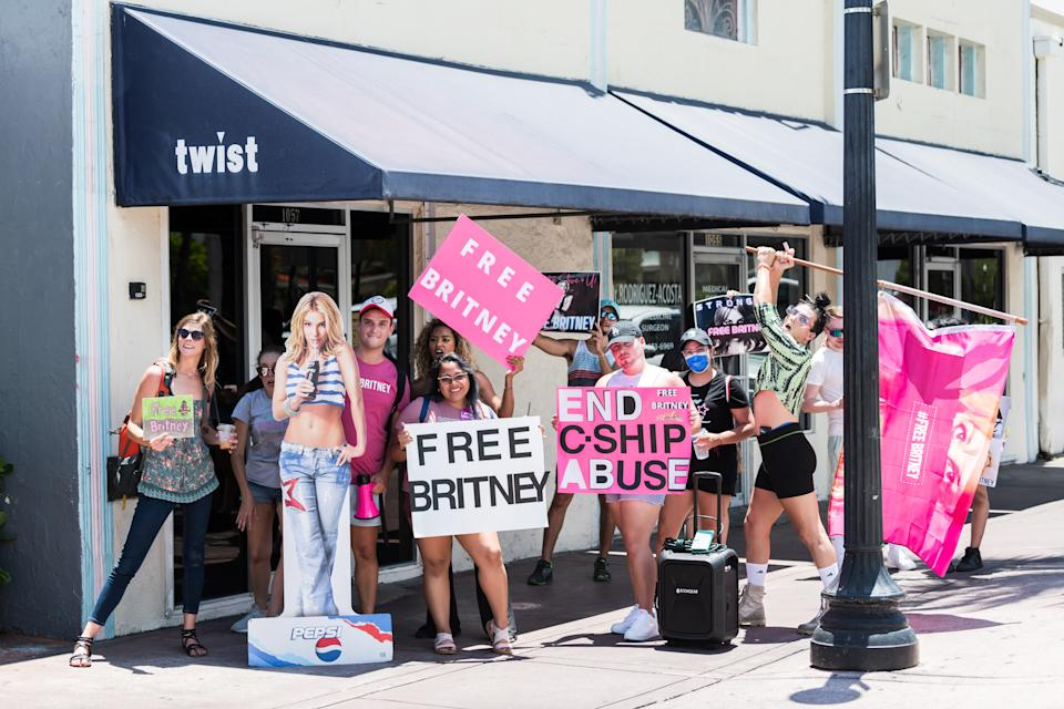 MIAMI BEACH, FLORIDA - AUGUST 07: Supporters of Britney Spears hold signs during a #FreeBritney rally in South Beach on August 07, 2021 in Miami Beach, Florida. Spears was placed in a conservatorship managed by her father, Jamie Spears, and an attorney, which controls her assets and business dealings, following her involuntary hospitalization in 2008. (Photo by Jason Koerner/Getty Images)