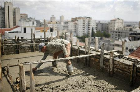 Palestinian worker flattens cement on the roof of a building under construction in Gaza