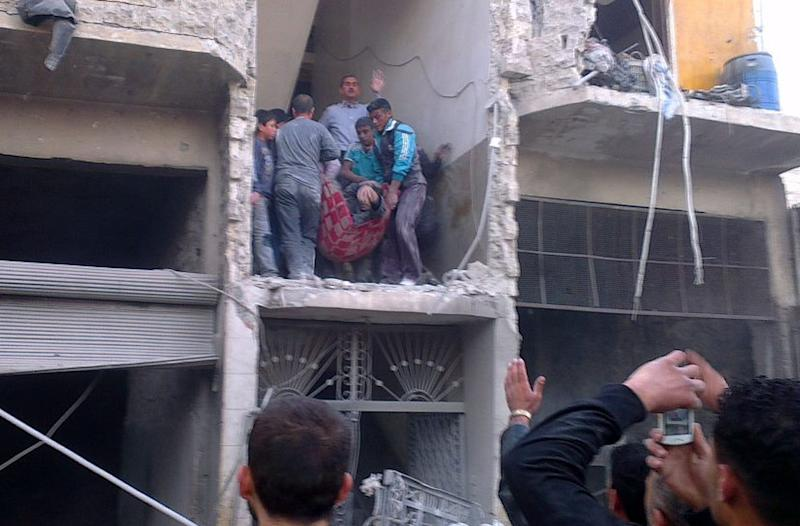 """Citizen journalism image provided by Aleppo Media Center AMC which has been authenticated based on its contents and other AP reporting, Syrian citizens carry an injured man from a damaged building that was hit by a Syrian forces airstrike, on the al-Marjeh neighborhood, of Aleppo, Syria, Tuesday March 19, 2013. Syria's information minister says a chemical weapon fired by rebels on a village in the north of the country is the """"first act"""" by the opposition interim government announced in Istanbul. (AP Photo/Aleppo Media Center, AMC)"""