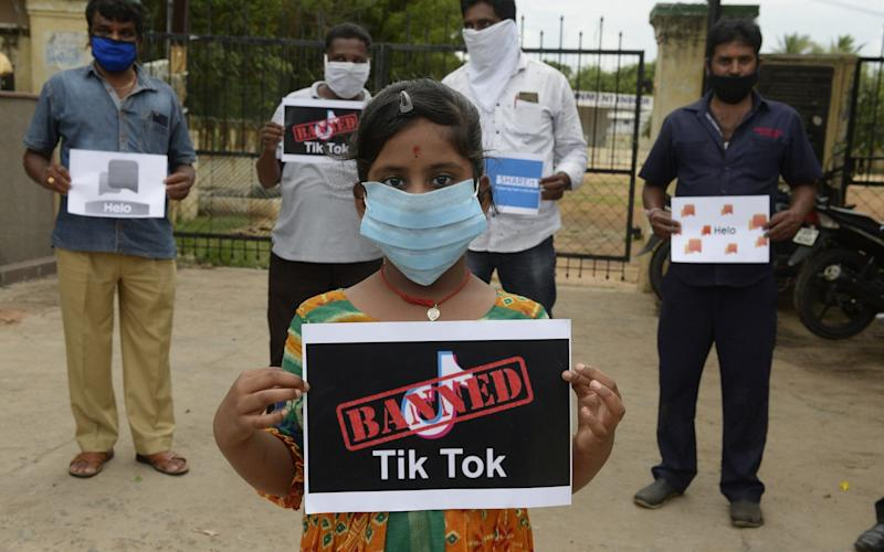 Members of the City Youth Organisation hold posters with the logos of Chinese apps in support of the Indian government for banning the wildly popular video-sharing 'Tik Tok' app, in Hyderabad on June 30, 2020 - Noah Seelam/AFP