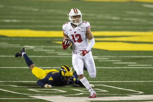 Wisconsin wide receiver Chimere Dike (13) gets away from Michigan defensive back Vincent Gray (4) during the first quarter of an NCAA college football game in Ann Arbor, Mich., Saturday, Nov. 14, 2020. (AP Photo/Tony Ding)