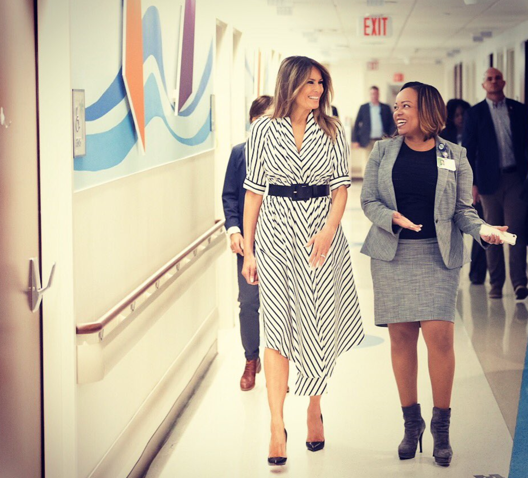 <p>While visiting a hospital, Melania rocked a $1,770 pleated striped dress by Adam Lippes. The designer had previously turned one of his fashion presentations into a statement in support of Planned Parenthood. (Photo: Twitter/Flotus) </p>