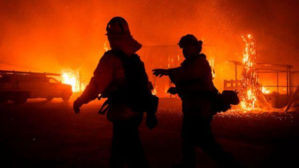 PHOTO: Firefighters give direction as a wind-driven fire burns a structure on a farm during the Kincade fire in Windsor, Calif., Oct. 27, 2019. (Philip Pacheco/AFP/Getty Images)