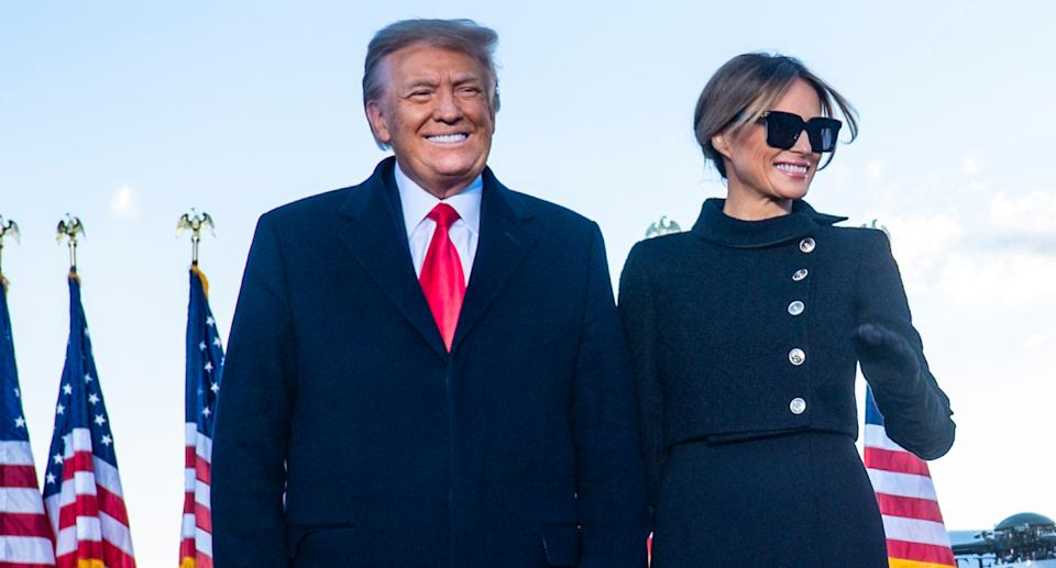 Donald Trump and wife Melania smiling for supporters.
