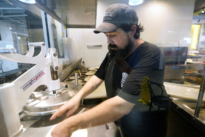 Nathan Glenn, who co-owns two restaurants across from the Jackson Women's Health Organization clinic, presses dough as he prepares for the next day's lunch crowd, in Jackson, Miss., Wednesday, May 19, 2021. He said his family has been in business there about 20 years, and when the restaurants opened he didn't know they were near an abortion clinic. He said he respects people's right to protest but they block the entrance to the restaurants and yell at his diners and the patrons of other businesses in the area. (AP Photo/Rogelio V. Solis)