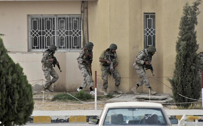Pakistani security forces prepare to storm a hospital building during a gun battle in Quetta, Pakistan, Saturday, June 15, 2013. Gunmen took over parts of a hospital in southwestern Pakistan Saturday after a bomb went off inside its emergency room, officials said. Several people died before authorities stormed the building and freed the hostages trapped inside. (AP Photo/Arshad Butt)