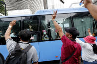 Pro-democracy protesters gestures to flash three-fingered salutes to a bus in Bangkok, Thailand, Sunday, Oct. 25, 2020. Thailand's government and the country's pro-democracy movement appeared no closer to resolving their differences Saturday, as the protesters' deadline for Prime Minister Prayuth Chan-ocha to step down came and went with no new action from either side, and no backing down. (AP Photo/Sakchai Lalit)