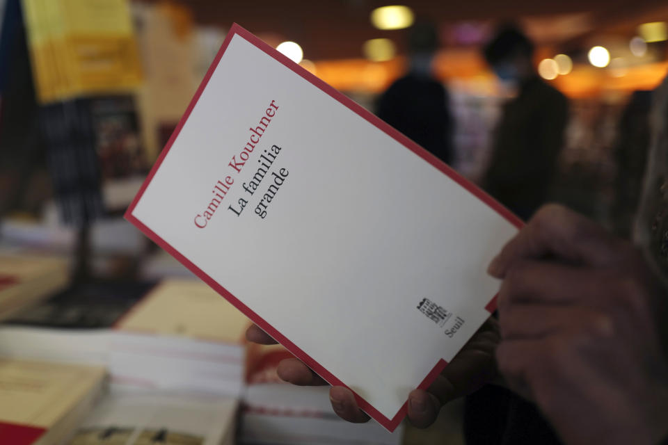 A person holds the book La Familia Grande, by Camille Kouchner, in a bookstore of Paris, Wednesday, Jan. 20, 2021. The book written by prominent French political expert Olivier Duhamel's stepdaughter, Camille Kouchner, accused him of abusing her twin brother during the late 1980s, when the siblings were 13-years-old. The French government pledged on Thursday to toughen laws on the rape of children, as a massive online movement has seen hundreds of victims share accounts about sexual abuses within their families under the hashtag #MeTooInceste. (AP Photo/Francois Mori)