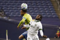 Seattle Sounders' Jordy Delem (8) heads the ball in front of Portland Timbers' Yimmi Chara in the first half of an MLS soccer match, Thursday, Oct. 22, 2020, in Seattle. (AP Photo/Elaine Thompson)