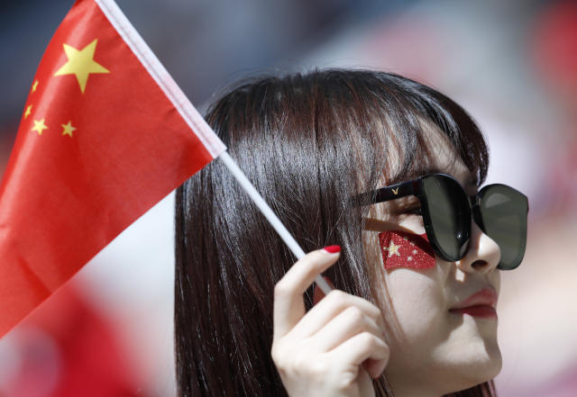 FILE - In this Wednesday, June 20, 2018 file photo, a woman holds a Chinese flag prior to the group B match between Portugal and Morocco at the 2018 soccer World Cup in the Luzhniki Stadium in Moscow, Russia, Wednesday, June 20, 2018. Chinese sponsors are more visible than ever and tens of thousands of Chinese fans have descended on Moscow, using their growing economic clout to secure top-dollar seats and dreaming of the day, perhaps not that far off, when China will host football's showcase. (AP Photo/Hassan Ammar, File)