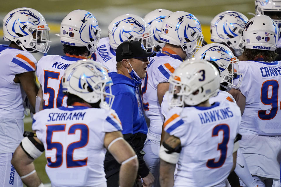 Boise State head coach Bryan Harsin, center, speaks with his players during the second half of an NCAA college football game against San Jose State for the Mountain West championship, Saturday, Dec. 19, 2020, in Las Vegas. (AP Photo/John Locher)