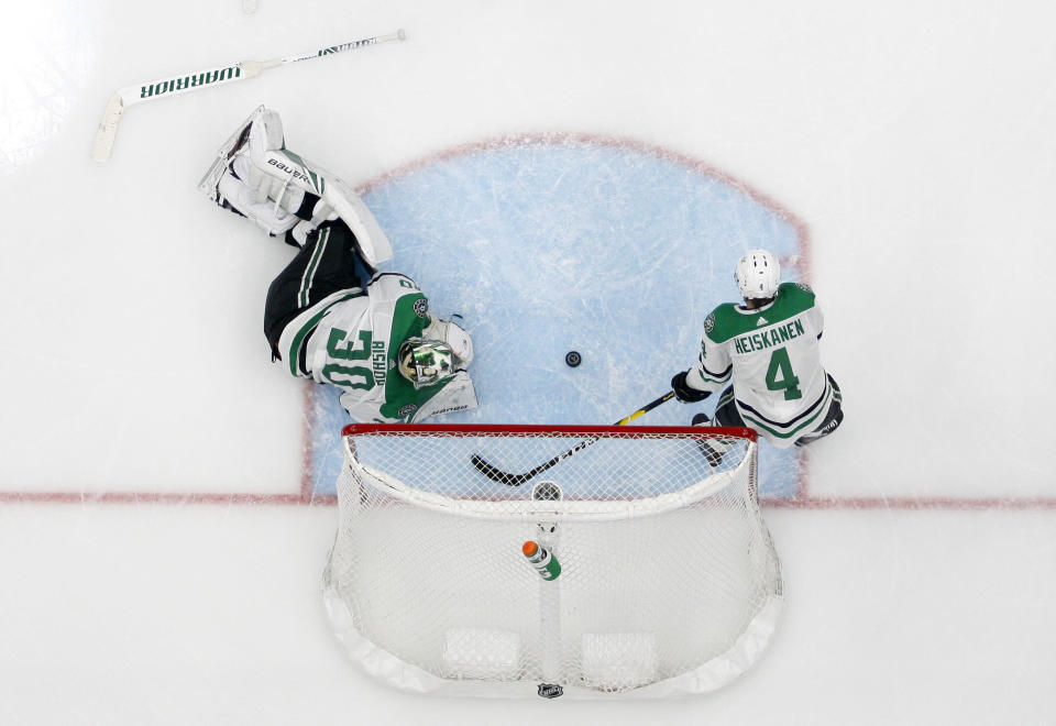 Dallas Stars' Ben Bishop (30) and Miro Heiskanen (4) lie by the net after giving up a score to St. Louis Blues' Pat Maroon during the second overtime in Game 7 of an NHL second-round hockey playoff series Tuesday, May 7, 2019, in St. Louis. The Blues won 2-1. (AP Photo/Jeff Roberson)
