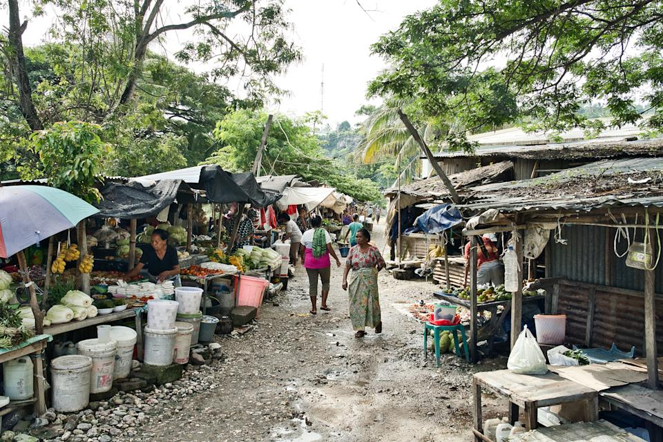 People buying food at basic outdoor fruit and food market in the city of Baucau, Timor Leste (East Timor) 10 March 2020