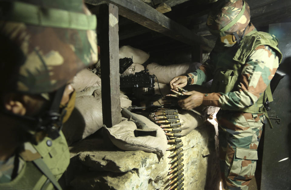 FILE - In this Dec. 18, 2020, file photo, Indian army soldiers prepare a light machine gun in their bunker at a forward post along the Line of Control (LOC) between India and Pakistan border in Poonch, about 250 kilometers (156 miles) from Jammu, India. The Line of Control, a highly militarized de facto border that divides the disputed region between the two nuclear-armed rivals India and Pakistan, and a site of hundreds of deaths, is unusually quiet after the two South Asian neighbors agreed in February, 2021, to reaffirm their 2003 cease-fire accord. (AP Photo/Channi Anand, File)