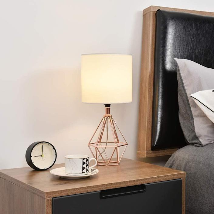 """You can pick between a black, gold or rose gold base with this lamp. It's perfect for small spaces since it won't take up too much room. Besides the geometric base, it also comes with a white lampshade. You will have to get a E26 bulb for it. <a href=""""https://amzn.to/32xzky8"""" rel=""""nofollow noopener"""" target=""""_blank"""" data-ylk=""""slk:Find it for $37 at Amazon"""" class=""""link rapid-noclick-resp"""">Find it for $37 at Amazon</a>."""
