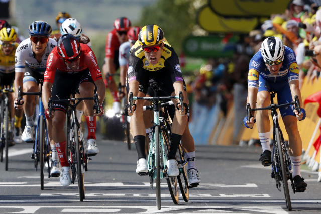 Belgium's Wout Van Aert, center, sprints to win the tenth stage of the Tour de France cycling race over 217 kilometers (135 miles) with start in Saint-Flour and finish in Albi, France, Monday, July 15, 2019. (AP Photo/ Thibault Camus)