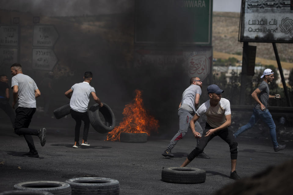 Palestinian demonstrators throws stones during clashes with Israeli security forces at the Hawara checkpoint, south of the West Bank city of Nablus Friday, May 21, 2021. (AP Photo/Majdi Mohammed)