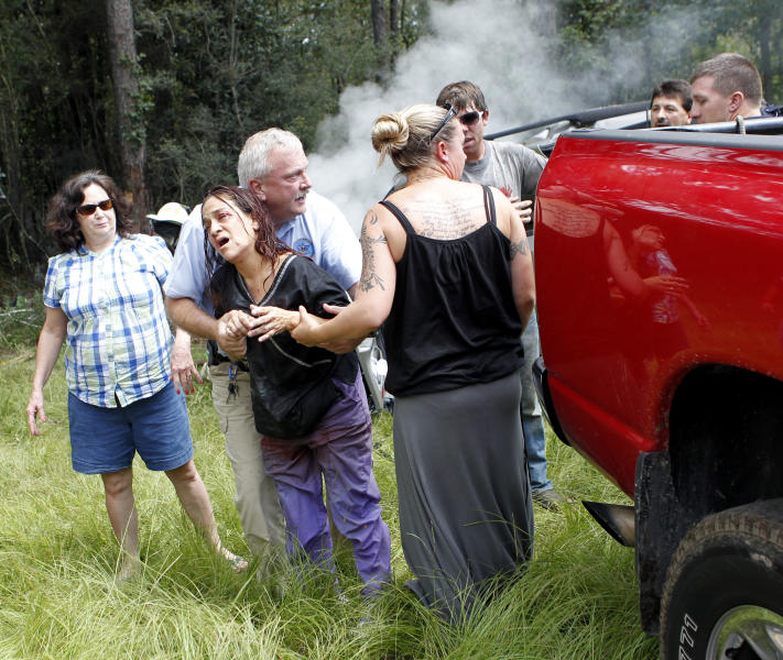 CORRECTS THAT DISABLED WOMAN IS THE DRIVER'S SISTER, NOT HER CHILD -  Passers-by  hold a woman after they rescued her from being pinned in a burning car on Interstate 10 in Hancock County, Miss., Thursday, Aug. 16, 2012. The fire was extinguished by the hose of a cement mixer, and fire extinguishers from nearby truckers. The woman was then extricated from the wreckage by the civilians as rescue personnel arrived, and she and her disabled sister, who was removed from the wreckage earlier, were airlifted from the scene. (AP Photo/Gerald Herbert)