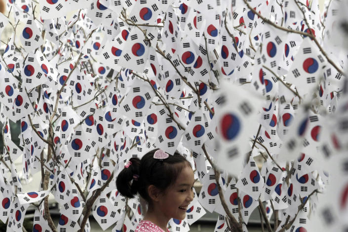 A girl is surrounded by small South Korean national flags set up to celebrate the Aug. 15 Korean Liberation Day from Japanese colonial rule in 1945, in Seoul, South Korea, Sunday, Aug. 14, 2011. (AP Photo/Ahn Young-joon)