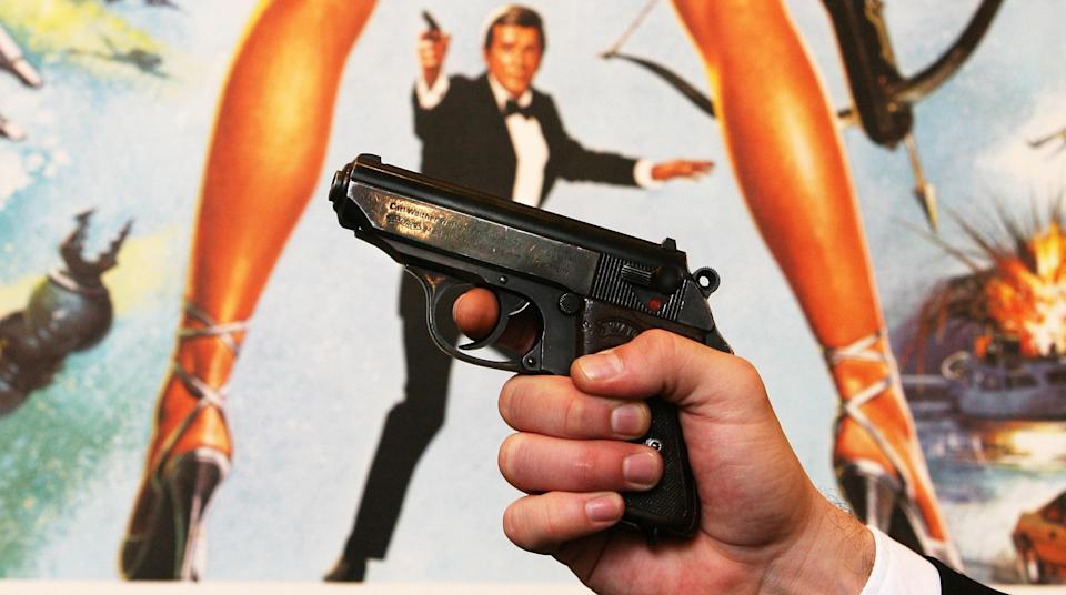 A Walther PPK handgun in front of a poster of the film 'For Your Eyes Only' at Christie's in London before the auction of a variety of weapons from James Bond films.   (Photo by Lewis Whyld - PA Images/PA Images via Getty Images)