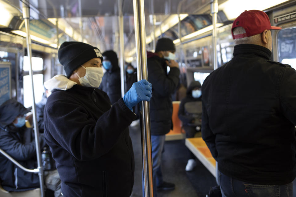 A subway rider wears a glove while holding a pole as several riders wear face masks during the coronavirus outbreak on the D train in the Brooklyn borough of New York on Wednesday, March 25, 2020. (AP Photo/David Boe)
