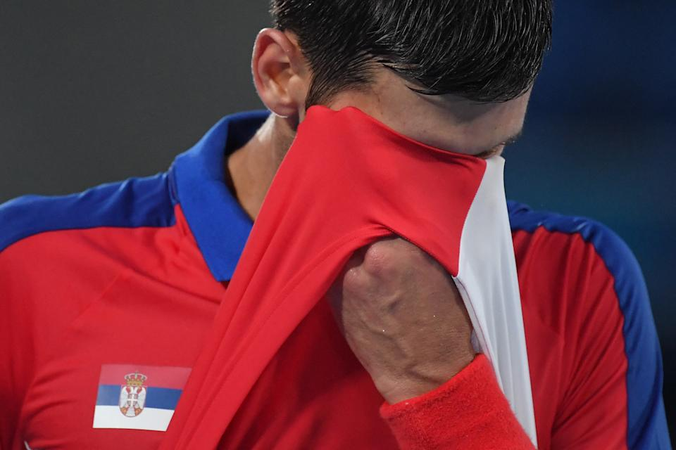 Serbia's Novak Djokovic wipes his face as he competes against Germany's Alexander Zverev during their Tokyo 2020 Olympic Games men's singles semifinal tennis match at the Ariake Tennis Park in Tokyo on July 30, 2021. (Photo by Tiziana FABI / AFP) (Photo by TIZIANA FABI/AFP via Getty Images)