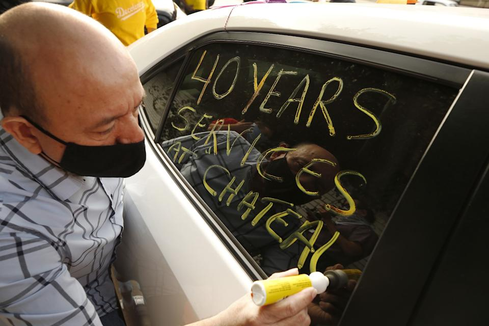 Valet worker Carlos Barrera writes a message on his car window in support of Chateau Marmont employees who lost their jobs.