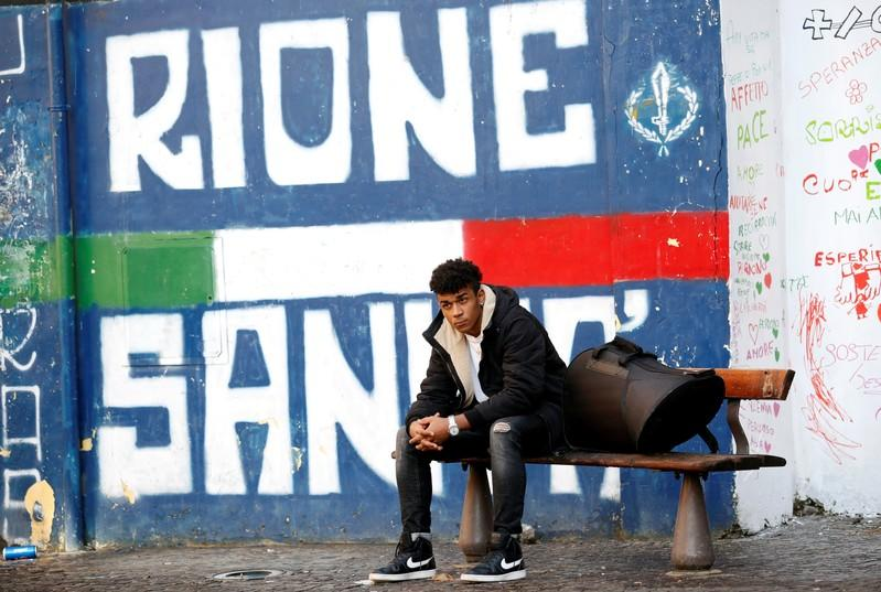 Nico Rodrigues, 21, seats on a bench, with his French horn in a case, outside the Santa Maria della Sanita Basilica in the Rione Sanita neighbourhood in Naples