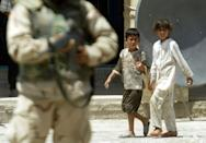 Iraqi children walk past a US soldier in Tikrit north of Baghdad, the hometown of toppled Iraqi leader Saddam Hussein, during a patrol in August 2003 (AFP/MARWAN NAAMANI)
