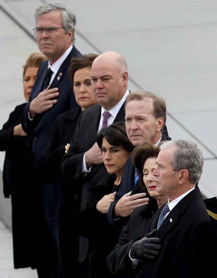Former President George W. Bush (R) and his wife Laura watch as a U.S. military honor guard team carries the flag draped casket of former President George H. W. Bush from the U.S. Capitol Dec. 5, 2018 in Washington, D.C. (Photo: Win McNamee/Getty Images)