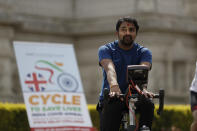 """A man takes part in """"Cycle to Save Lives"""" a 48 hour, non-stop static relay cycle challenge at the BAPS Shri Swaminarayan Mandir, also know as the Neasden Temple, the largest Hindu temple in the UK, in north London, to raise money to help coronavirus relief efforts in India, Saturday, May 1, 2021. The challenge sees people combining at three different venues in the UK, cycling in a static relay the equivalent distance of 7,600 Km, which is the distance from London to Delhi. (AP Photo/Matt Dunham)"""