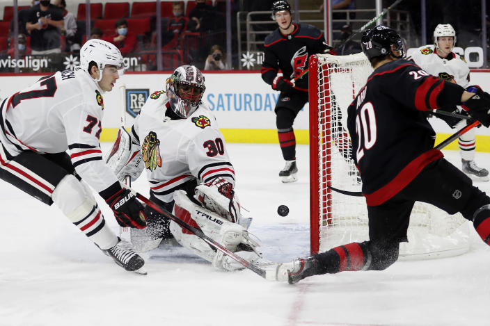 Carolina Hurricanes' Sebastian Aho (20) slips the puck past Chicago Blackhawks goaltender Malcolm Subban (30) with Blackhawks' Kirby Dach (77) nearby for a goal during the second period of an NHL hockey game in Raleigh, N.C., Monday, May 3, 2021. (AP Photo/Karl B DeBlaker)