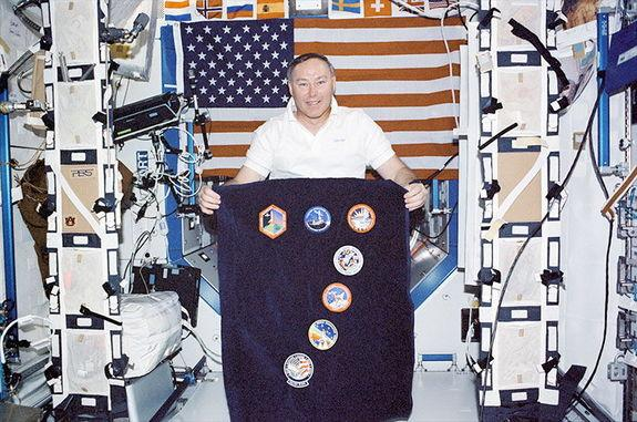 On board the International Space Station in 2002, astronaut Jerry Ross displays the mission logos representing the record seven space shuttle missions he has flown