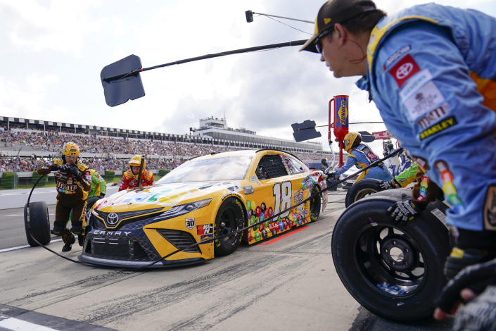 The crew for Kyle Busch (18) work on the car during a pit stop during a NASCAR Cup Series auto race at Pocono Raceway, Saturday, June 26, 2021, in Long Pond, Pa. (AP Photo/Matt Slocum)