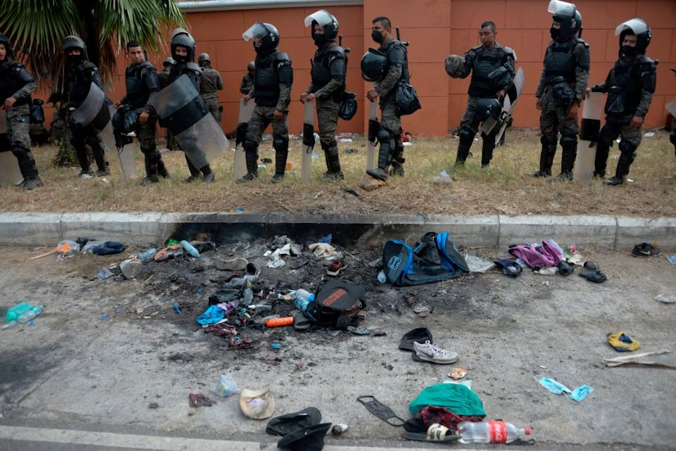 Belongings of Honduran migrants remain next to soldiers of Guatemalan Army after a violent clash. Source: Getty