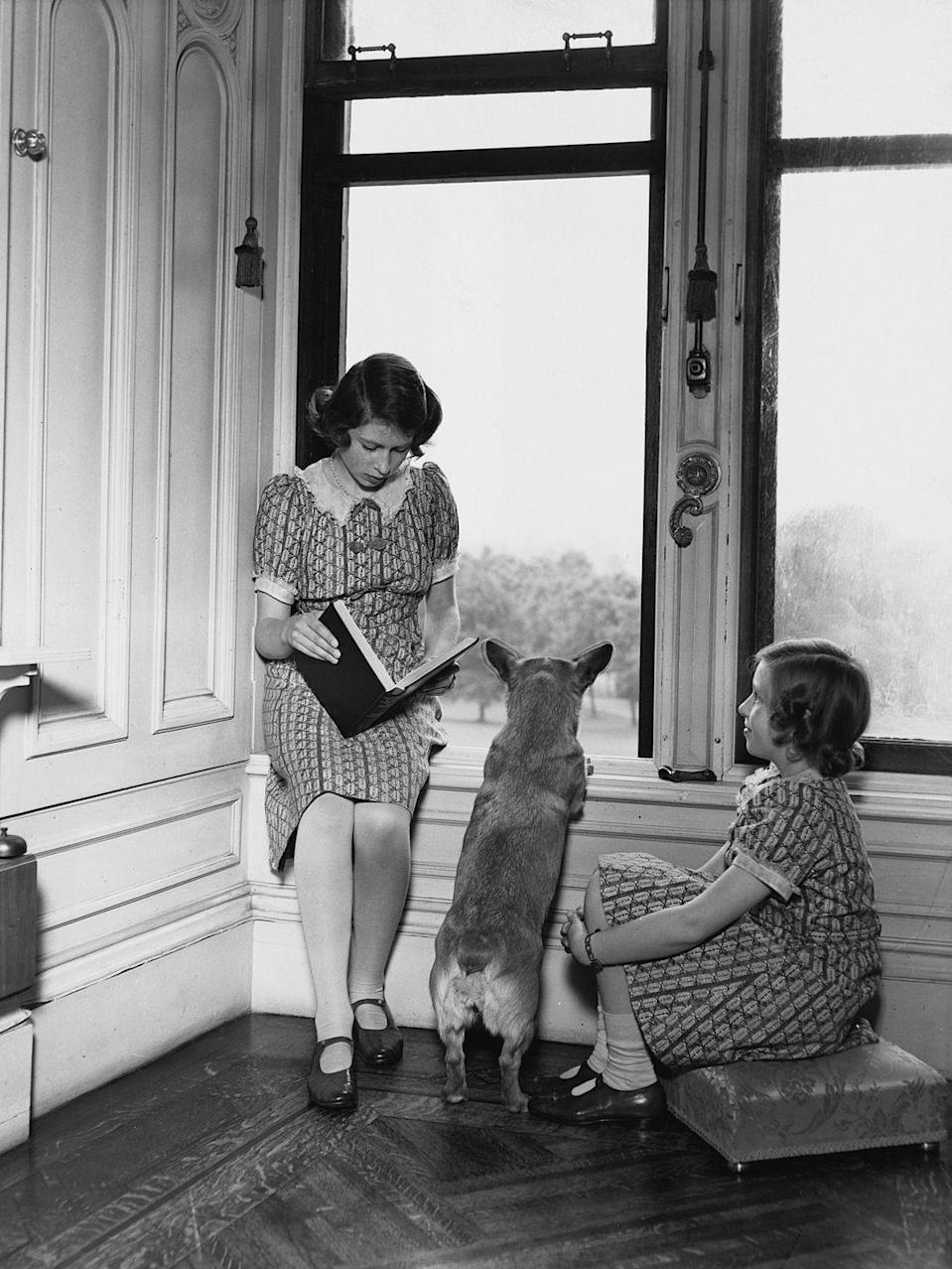 <p>Princess Elizabeth reads to her sister as Jane, the family corgi, looks out the window at Windsor Castle. Don't miss their matching dresses.</p>