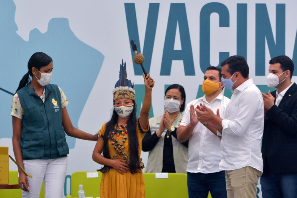TOPSHOT - Witoto's Indigenous Nurse Vanda Ortega (C) is seen showing her vaccine certificate after becomimg the first person to be inoculated with the Sinovac Biotech's CoronaVac vaccine against Covid-19 in Manaus, Amazonas state, Brazil, on January 18, 2021. (Photo by Marcio JAMES / AFP) (Photo by MARCIO JAMES/AFP via Getty Images)