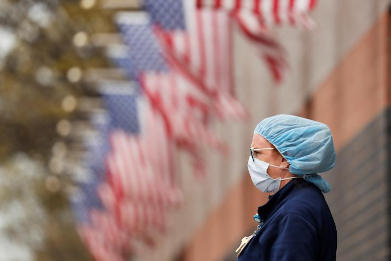A nurse wearing personal protective equipment watches an ambulance driving away outside of Elmhurst Hospital during the ongoing outbreak of the coronavirus disease (COVID-19) in the Queens borough of New York, U.S., April 20, 2020. REUTERS/Lucas Jackson TPX IMAGES OF THE DAY