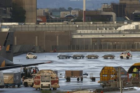An airport vehicle pulls four cargo platforms with coffins on the tarmac at the Marseille Provence Airport in Marignane, France, June 9, 2015 as Lufthansa prepares to transport coffins with the remains of 44 victims of the Germanwings Airbus A320 crash from Marseille, France, to Duesseldorf, Germany. REUTERS/Jean-Paul Pelissier