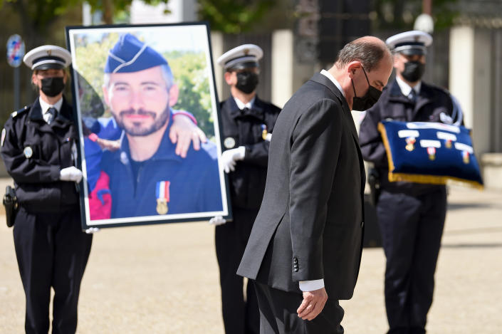 French Prime Minister Jean Castex walks past a portrait of police officer Eric Masson, who was killed during an anti-drug operation, during an hommage ceremony in Avignon, southern France, Tuesday, May 11, 2021. It was the latest of several attacks targeting French police that have angered police unions and become a political issue ahead of regional elections in June and next year's presidential election. France's prime minister is proposing tougher and faster punishment for people who attack police, as the government pays a national tribute to the latest police officer killed in the line of duty. (Nicolas Tucat, Pool via AP)