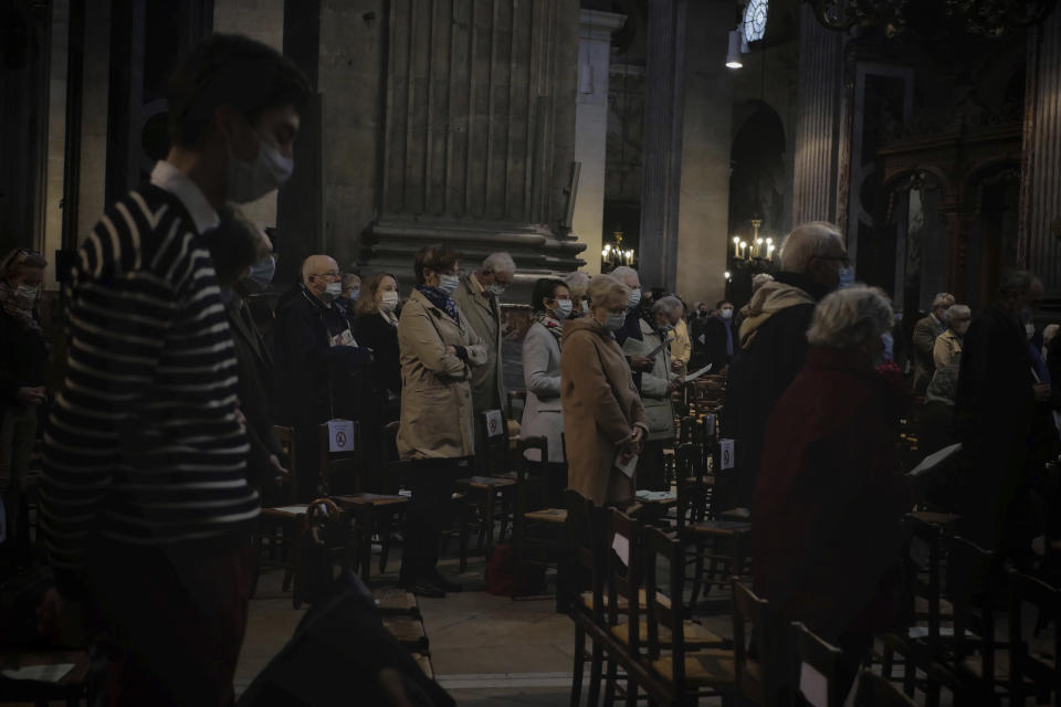 Catholic worshippers attend the All Saints Day mass in Saint-Sulpice church, in Paris, Sunday, Nov. 1, 2020. France heightened its security alert amid religious and geopolitical tensions around cartoons mocking the Muslim prophet. (AP Photo/Thibault Camus)