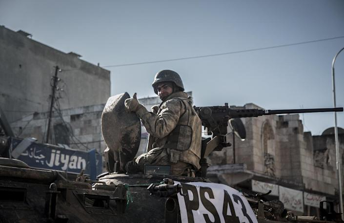 A Turkish soldier thumbs up on top of an army vehicle in a street of the Syrian town of Kobane, (aka Ain al-Arab) on February 22, 2015, during an operation to relieve the garrison guarding the Suleyman Shah mausoleum in northern Syria (AFP Photo/Mursel Coban)