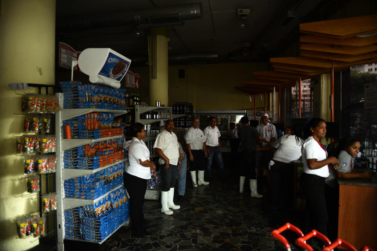 Employees of a supermarket closed due to a blackout, wait for power to be re-established, in Caracas on September 3, 2013. Major power blackouts paralyzed Venezuela's capital and several states across the country on Tuesday but there was no official explanation for the cause. AFP PHOTO/Juan Barreto (AFP | Juan Barreto)