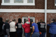 People pray as they hold their hands on a prayer wall outside of the historic Vernon African Methodist Episcopal Church in the Greenwood neighborhood during the centennial of the Tulsa Race Massacre, Monday, May 31, 2021, in Tulsa, Okla. The church was largely destroyed when a white mob descended on the prosperous Black neighborhood in 1921, burning, killing, looting and leveling a 35-square-block area. (AP Photo/John Locher)