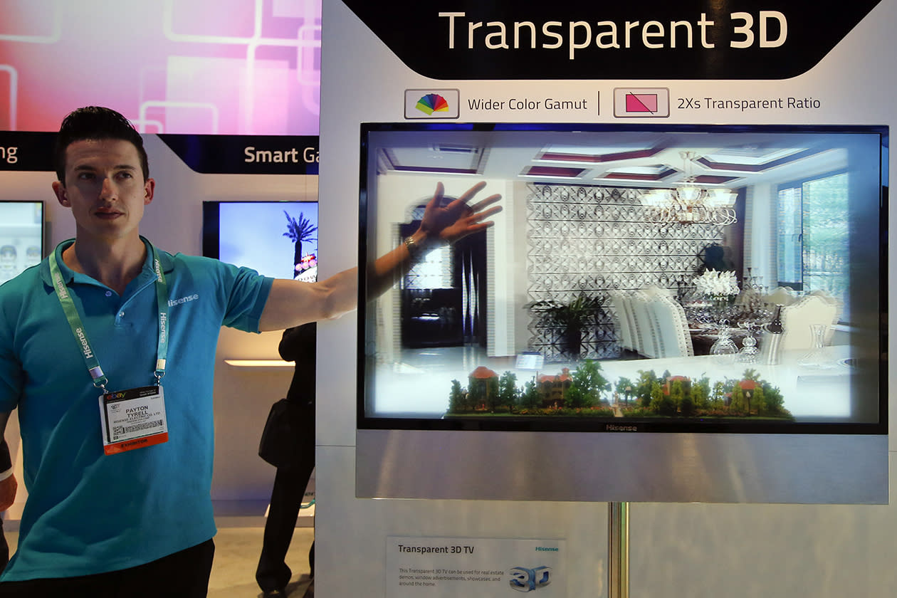Payton Tyrell, left, demonstrates on a transparent 3D TV at the Hisense booth at the International Consumer Electronics Show.